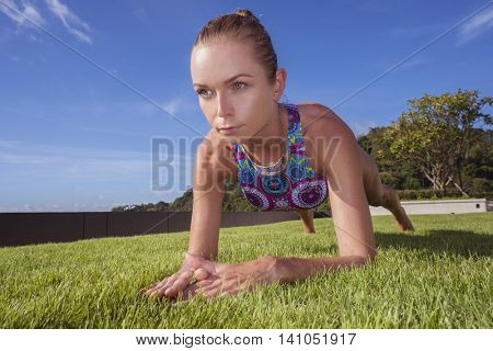 Bottom front view of pony tailed pretty blonde woman wearing colourful bikini doing plank position on a green grass rooftop over blue sky. Sport and healthy lifestyle concept