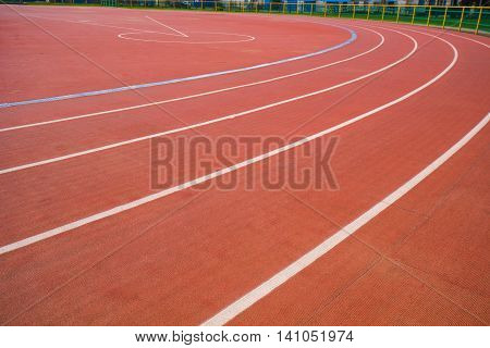 Red running track with white stripes in stadium for athlete, jogging, relax, walk and running