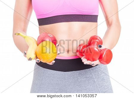Close-up Of Woman Holding Dumbbells And Fruits