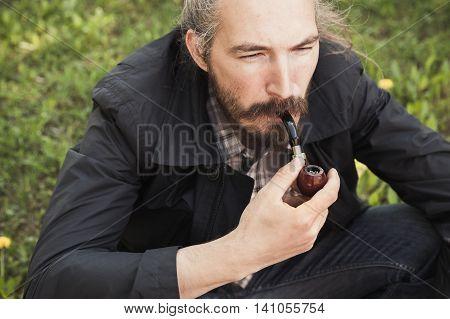 Asian Man Smoking A Pipe On Grass