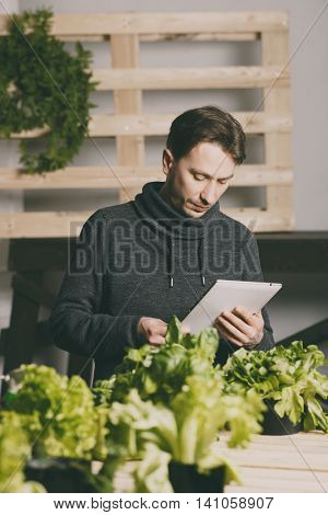 Handsome modern grower using his tablet while growing plants indoor.