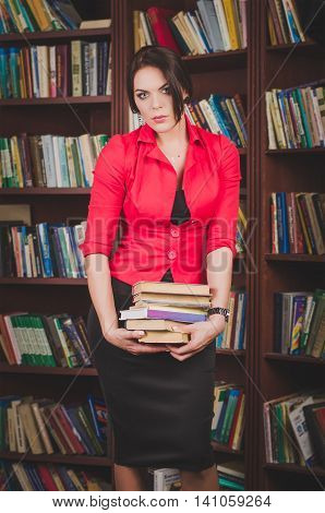 Beautiful Young Brown-haired Woman In Office Attire Standing Near Bookshelves And Holds A Stack Of B