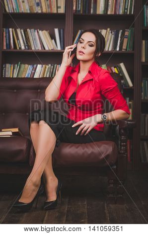 Attractive Business Woman In Office Clothes Sitting On A Leather