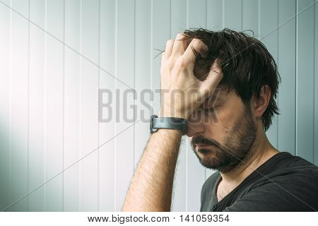 Profile portrait od miserable troubled man with serious expression depressive male with hand on face.