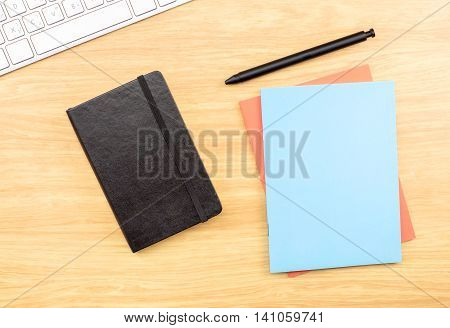 Blank Black,blue And Orange Notebook ,pen And Keyboard On Wooden Table , Mock Up For Adding Your Des