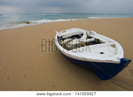 an old boat lying on yellow sand on the shore of the blue sea
