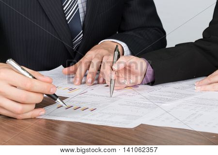 Closeup of Business People Analyzing Financial Figures
