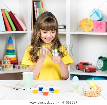 Easter holiday - beautiful smiling little girl with brush coloring eggs for easter
