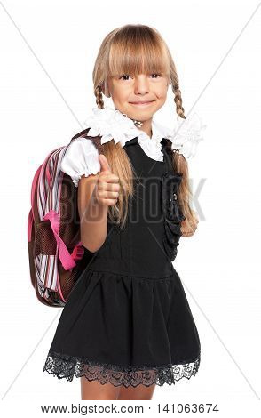Happy little girl. Smiling little girl with backpack showing her thumbs up, isolated on white background.
