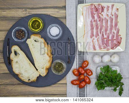 Top view of ingredients for Bruschetta with bacon tomatoes herbs and oil on toasted garlic cheese bread ciabatta