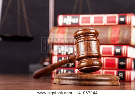 Close-up of Wooden gavel with golden scales of justice  and books on background