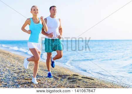 Couple running. Sport runners jogging on beach working out smiling happy. Fit male fitness model and attractive female jogger. Multiracial group, Asian woman and Caucasian man
