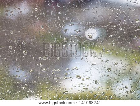rain drops on windowpane and blurred urban background