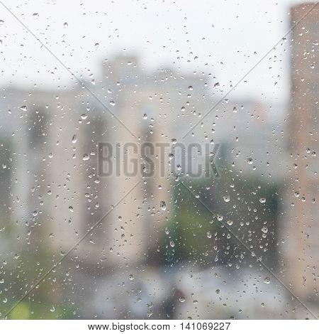 Rain Drops On Window Glass And Blurred Urban House