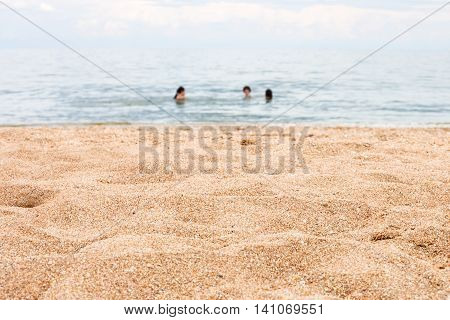Sand Beach And Blurred Swiming People In Sea