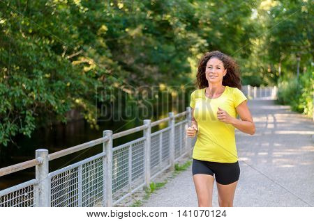 Athletic Fit Young Woman Jogging Along A Canal