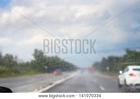 raindrops on windscreen during driving car in rain ( (focus on glass)