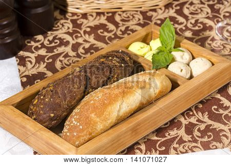 bread and baguettes with butter on a wooden plate