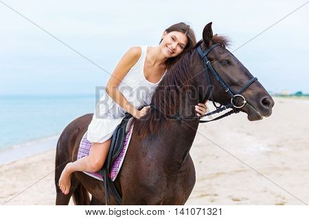 Smiling Equestrian Woman Riding On A Horse On The Beach