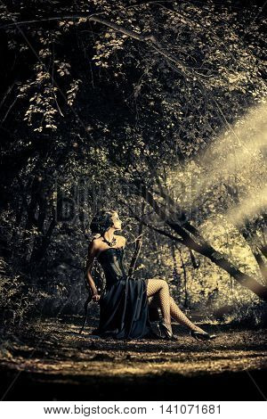 Beautiful gothic woman wearing long black dress posing in a mystic forest. Medieval history. Fashion.