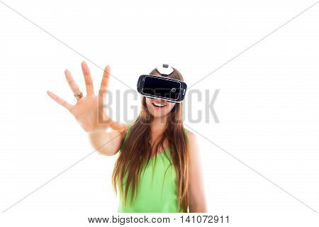 Portrait of happy smiling young beautiful girl getting experience using VR-headset glasses of virtual reality. Isolated