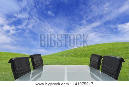 Modern meeting table over grass hill and sky