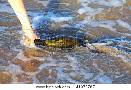 baby hand collecting bottle on the Beach