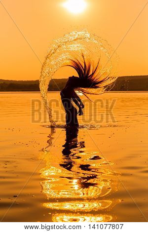 Silhouette of young girl in the water splashing their hair against sunset