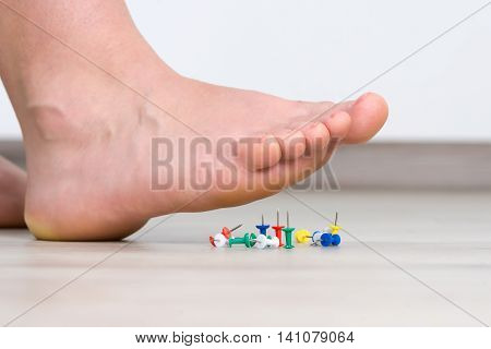 Female foot above colored pushpin, health feet