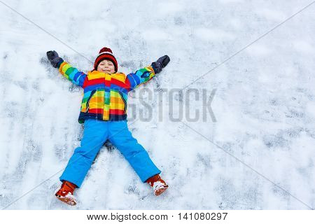 Cute little kid boy in colorful winter clothes making snow angel, laying down on snow. Active outdoors leisure with children in winter. Happy child