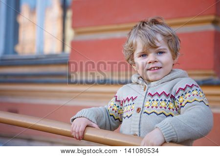Little caucasian toddler boy of two years having fun in spring city, outdoors