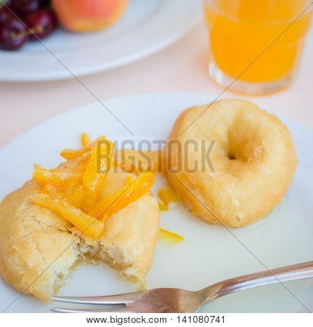 Breakfast including donuts with candied orange jam orange juice and fruits. Healthy breakfast. Good morning. Breakfast table. Morning breakfast with classic donuts and honey.
