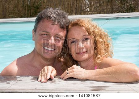 Happy Middle Aged Couple Relaxing On The Edge Of Swimming Pool