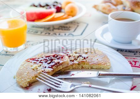 Breakfast table including pancakes with raspberry jam, coffee, orange juice, pastries and fruits. Healthy breakfast. Good morning. Morning breakfast with classic pancakes and jam. Selective focus.