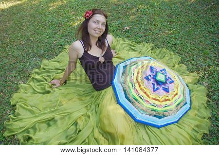 Girl brunette in a long green skirt with a bandage and a red flower on her head, she sits on the grass with big wicker native american mandala