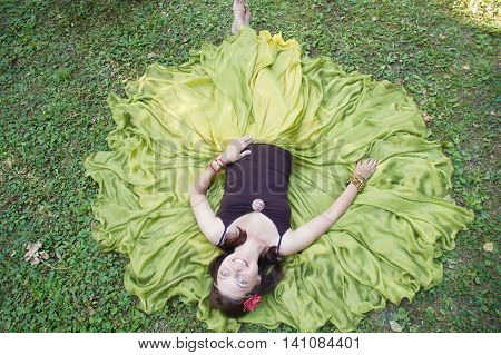 Girl brunette in a long green skirt with a bandage and a red flower on her head, she lies on the grass