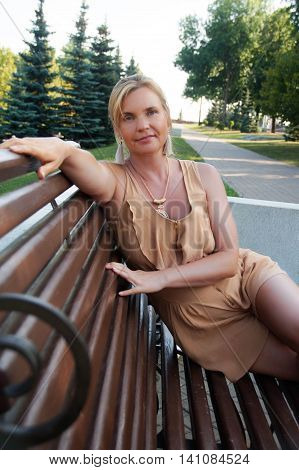woman in a light beige summer jumpsuit sitting on a bench in the park