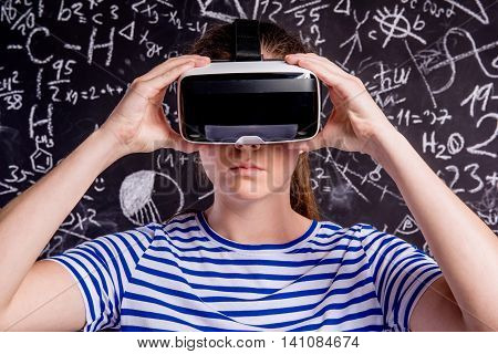 Beautiful woman in blue striped t-shirt wearing virtual reality goggles. Student against big blackboard with mathematical symbols and formulas. Studio shot on black background.