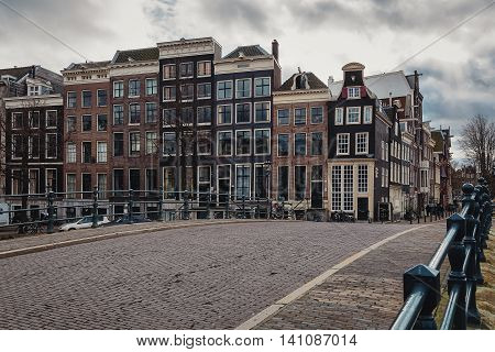 Look at the canal houses along the Amstel River in Amsterdam city center.
