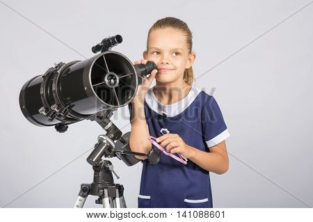 Seven-year Girl Standing Next To A Reflector Telescope And Looks Mysteriously Into The Sky