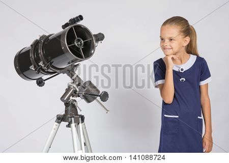 Seven-year Girl With Interest Looking At A Reflector Telescope