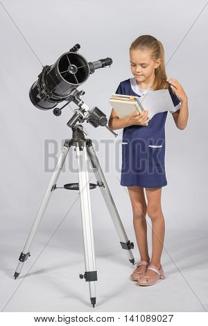 Schoolgirl Leafing Through A Textbook While Standing At The Telescope