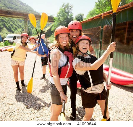 Team of five gathered for a picture, ready fr a rafting summer action.