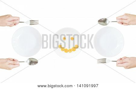 Closeup white ceramic dish with stainless fork and spoon in woman hand with smile face of cut carrot in dish at the center in top view isolated on white background in healthy food concept
