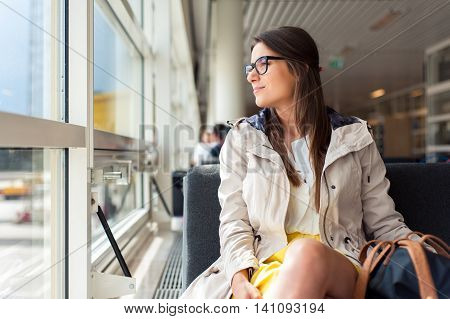 Casual woman in airport hall. Woman waiting her flight at airport terminal, sitting on chair and looking on the window.