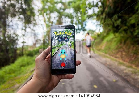 California, United States - July 23 2016 : Hand holding a cellphone to play Pokemon Go with blur background