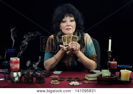 Middle-aged clairvoyant sits at the desk surrounded candles, fortune telling cards and bean grains. Black-haired woman holds three cards and looks at the camera. Horizontal indoors shot on black background