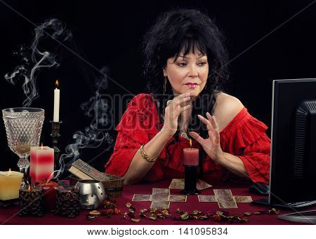 Middle-aged Gypsy woman predicting future online with fortune telling cards. Black-haired woman in red blouse looking at monitor during internet session. There are some cards and burning candles at the desk