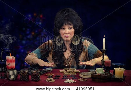 Middle-aged fortuneteller doing tarot cards reading. She sits at the desk with burning candles, tarot cards and bean grains. She holds hands over it and looks at the camera. Horizontal indoors shot on dark background