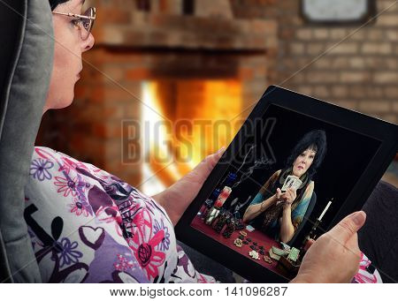 Middle-aged woman sits in a soft chair and holds tablet computer. In touchscreen, old black-haired female clairvoyant shows three fortune telling cards and looks at the client